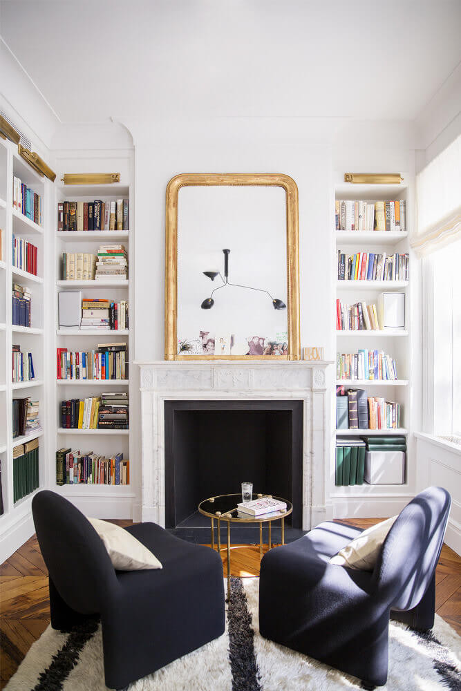 Ali Cayne's West Village townhouse. Home office. Vintage Beni Ourain Rug. Antique brass mirror above fireplace. Book shelves with brass library sconces above. Serge Mouille chandelier,