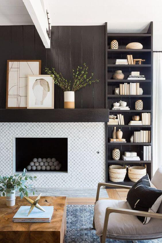 A subtle moroccan tiled fireplace is topped with a dark timber mantel. On the mantel sits two pieces of monochrome abstract paintings and a tall, two-toned ceramic vase with branches splayed out organically. To the right is a tall timber bookcase filled with books, baskets, ceramic pots and other decorative objects. The floors are honey oak. There is a blue persian style rug on the floor and there is a midcentury chair and timber coffee table with a plant and coffee table book with a gold decorative object sitting on top.