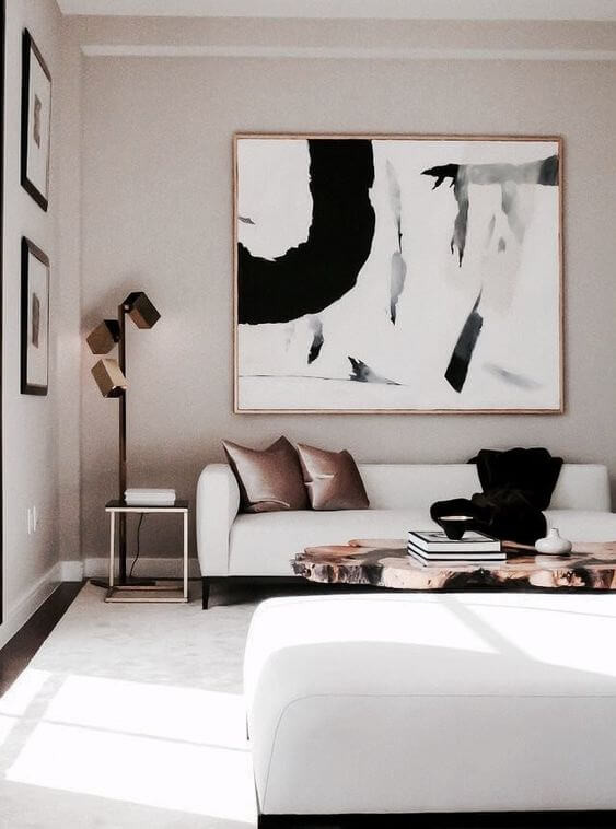 White sofas face each other with a mirrored coffee table with coffee table books on top. There is a brass three-cubed floor lamp in the corner and a large abstract black and white painting framed in brass hanging above one of the sofas. Two dusty pink cushions sit on the sofa below. The timber floors are covered with a white area rug.