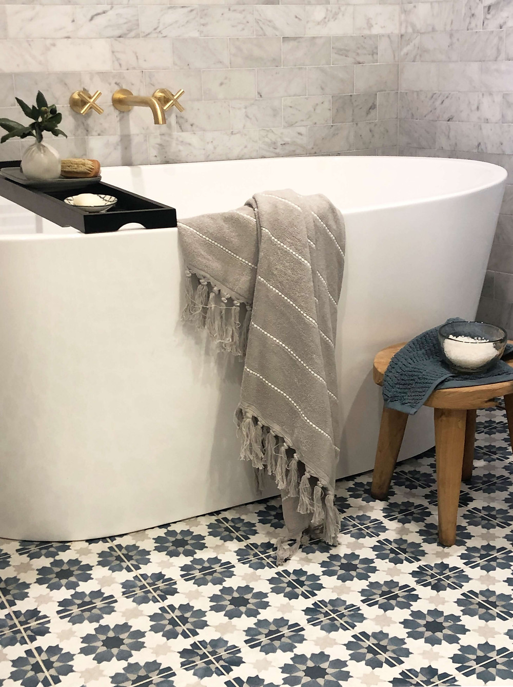 Carrara marble tile backsplash behind a white stand alone tub. Black bath tray with a flower vase and nail brush. A grey turkish towel draped over the side. Brass tapware mounted in the wall. Teal blue and grey flower Spanish tiles on the floor. A natural timber stool with a towel sitting just next to the tub.