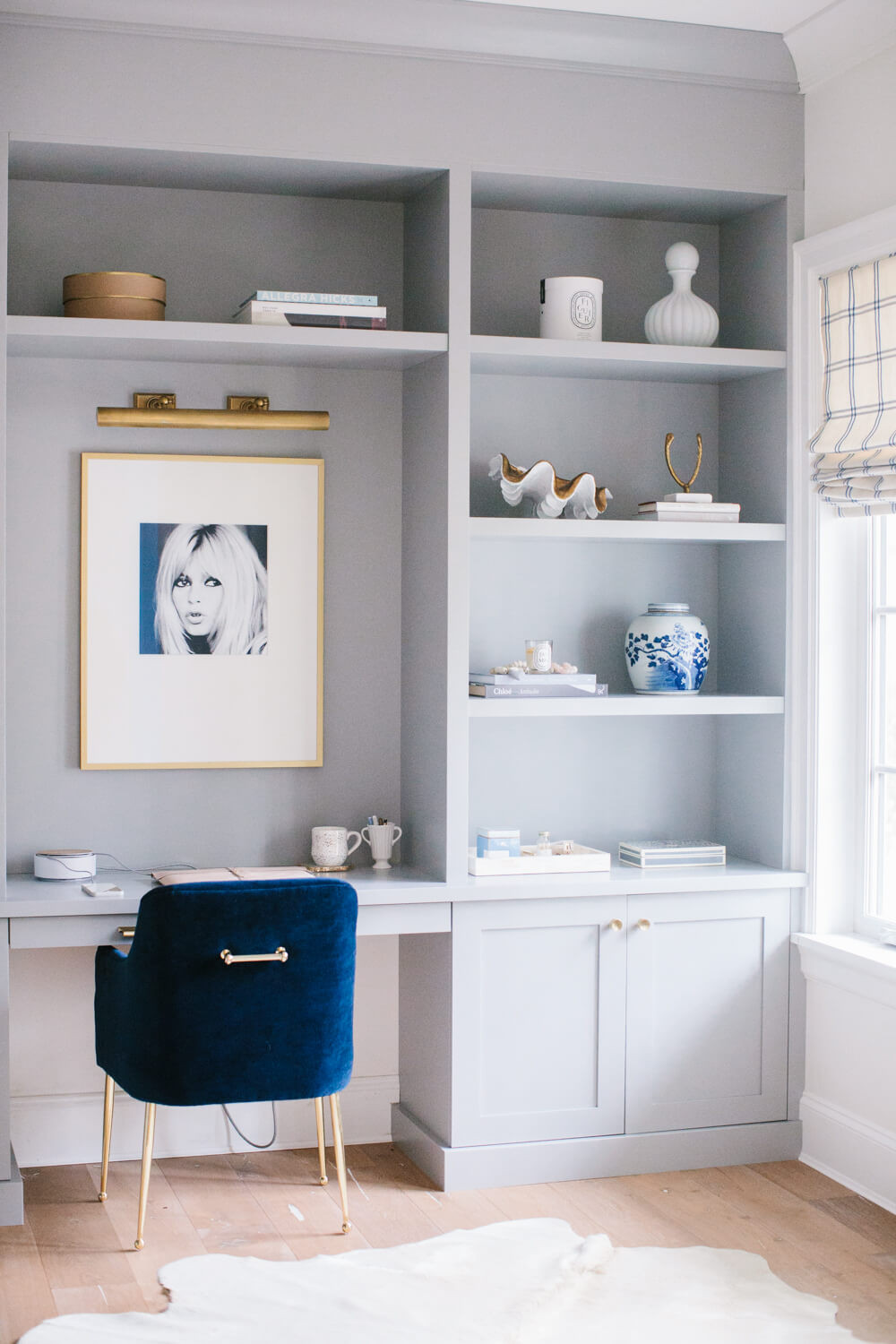 Grey custom built-in desk surrounded by stylish open shelving with vases, books and other decorative objects. Shaker cabinets at the bottom with brass hardware. The desk chair is a deep blue velvet with the added touch of a brass handle on the back to match its brass mid-century legs. On the grey wall in front of the desk is a pop art portrait of a skinny blonde lady likely from the 1960s with a brass library lamp mounted above to showcase the art work. On the adjacent window is a white and grey modern plaid patterned window shade. On the floor is a light oak timber layered with a white animal hide rug.