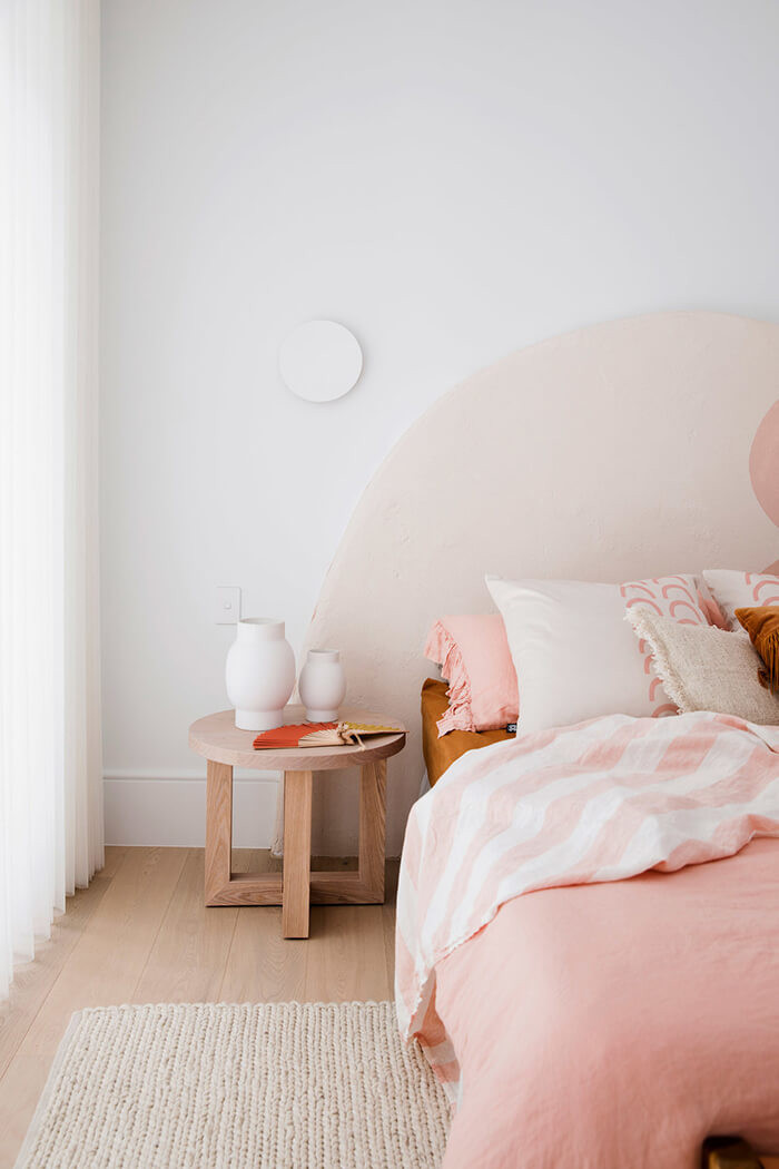 DIY arched headboard in a light and bright bedroom Scandinavian inspired decor with dusty pink bedding, blond timber side table and floor with comfy rug.