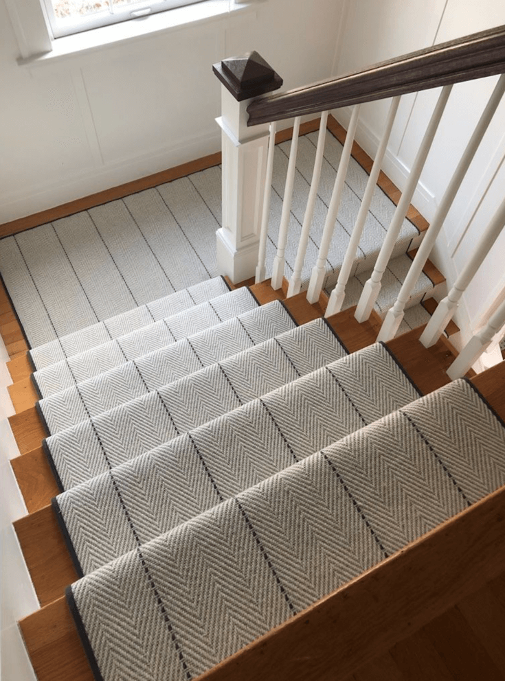 Charcoal striped, grey herringbone flatweave carpet runner on top of timber stairs. White and timber balustrade. White walls with narrow timber mouldings and white staircase window lets in natural light.