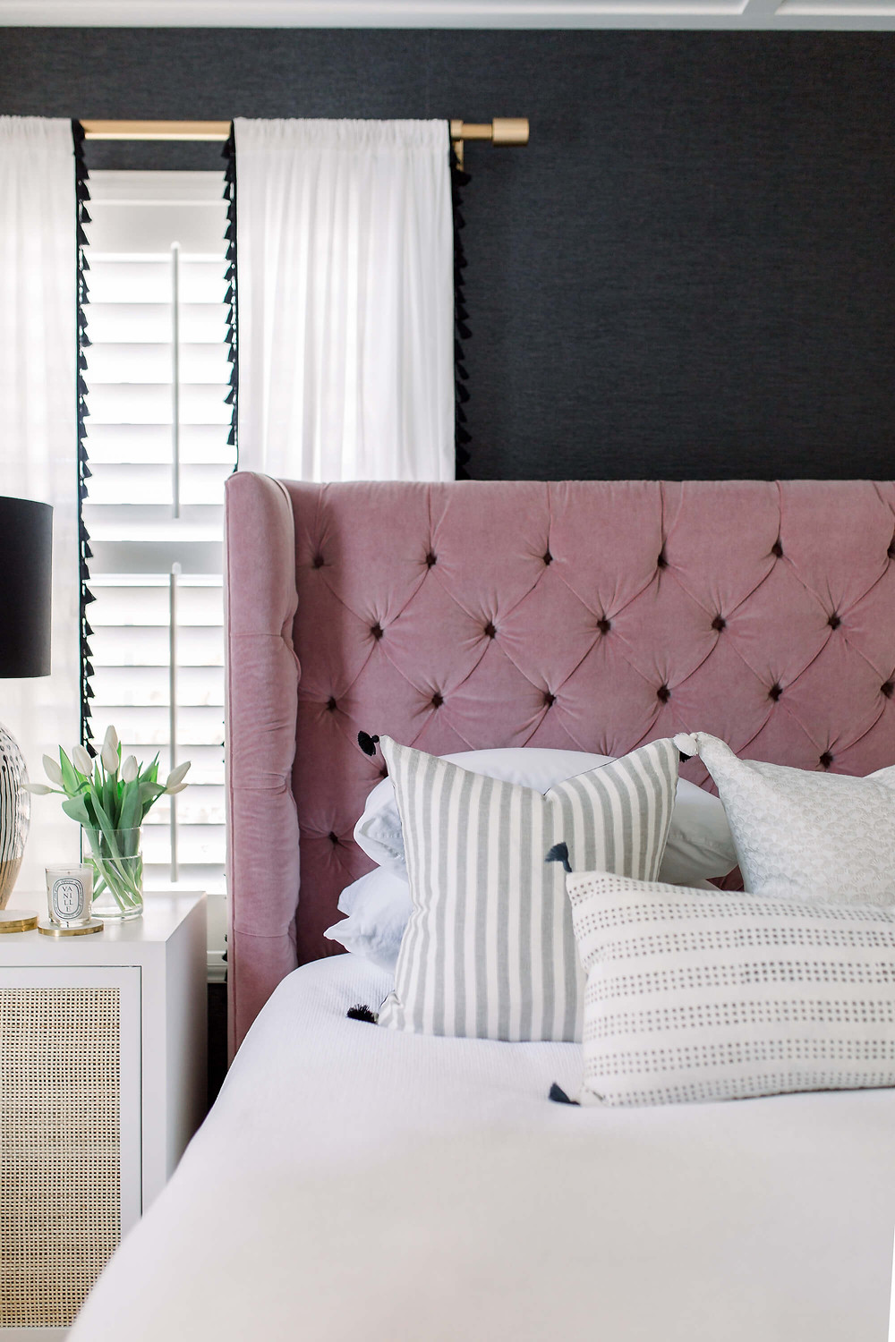 Dusty pink tufted headboard, white and grey striped cushions, black grass cloth wall paper. White drapes, plantation shutters and brass curtain rail.