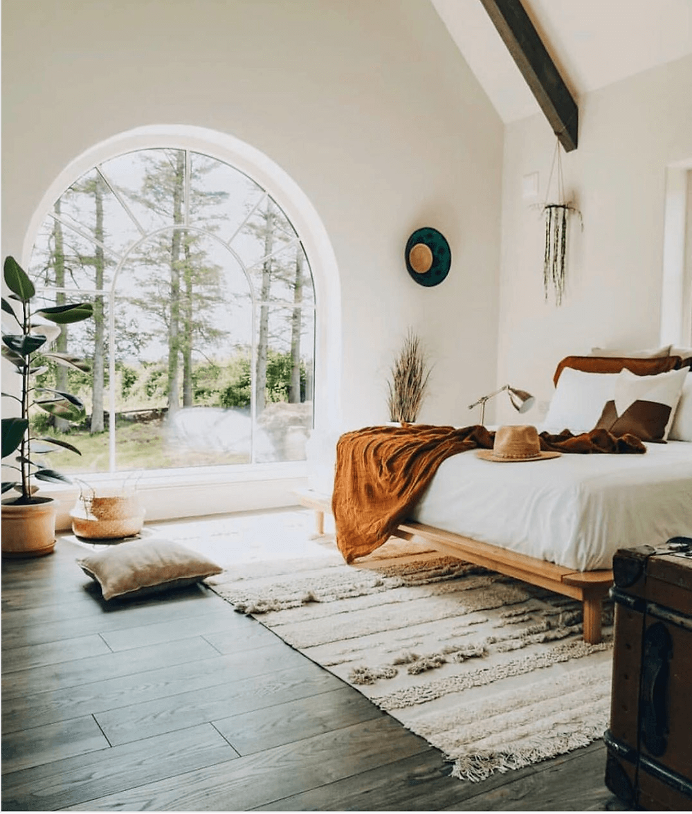 Natural bedroom. Arched window. Wooden beams on ceiling. Rust throw. Fiddle leaf plant.