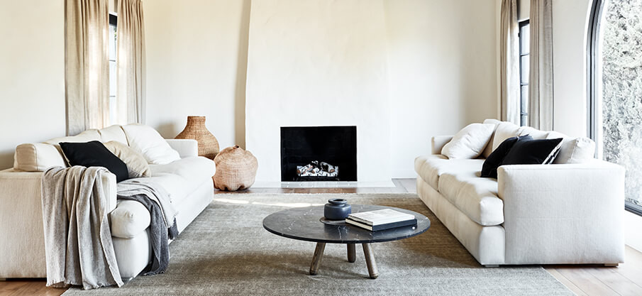 Eco-friendly living room with white washed walls and fireplace. White sofas, soft throws, handwoven rug with black marble coffee table. Sustainably sourced, fair trade.