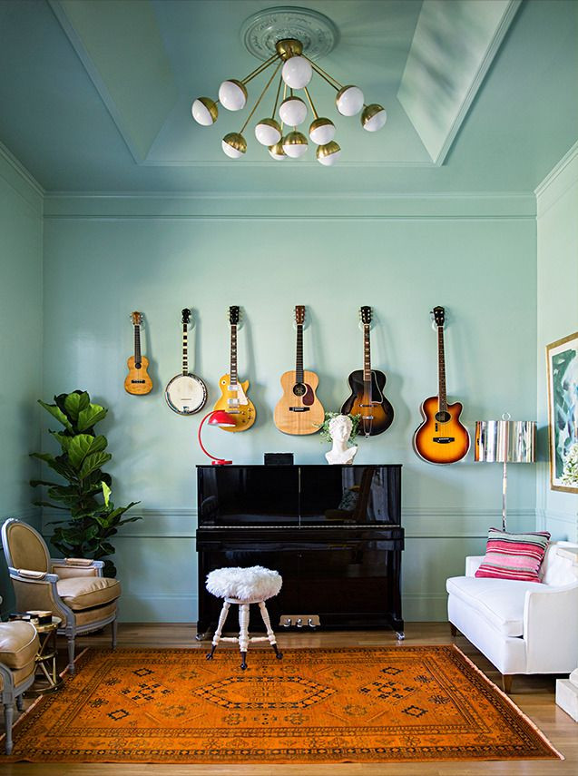 Guitars hung on a Tiffany Blue wall with matching ceiling. Mid-century light fixture. Bohemian rug. Piano in a music room.