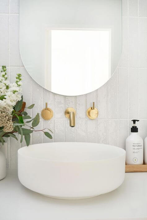 Vertical white subway tiles in bathroom behind vanity. Oval mirror on wall above wall mounted modern brass taps. White sink on top of marble vanity bench. Plants and soap on a timber tray flank the sink.