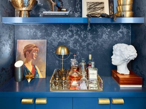 Antique vignette. Blue cabinetry. Brass hardware. Bar tray. Vintage painting and sculptural bust.