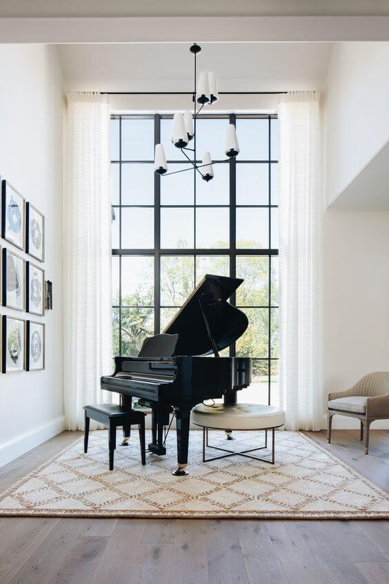 A white room with extra high ceilings features a baby grand piano. The piano sits on a black and white Beni Ourain rug and is framed by a large floor-to-ceiling window with white drapes. On the adjacent wall is a grid of six framed abstract art pieces and hanging from the ceiling over the piano is a black and white pendant.