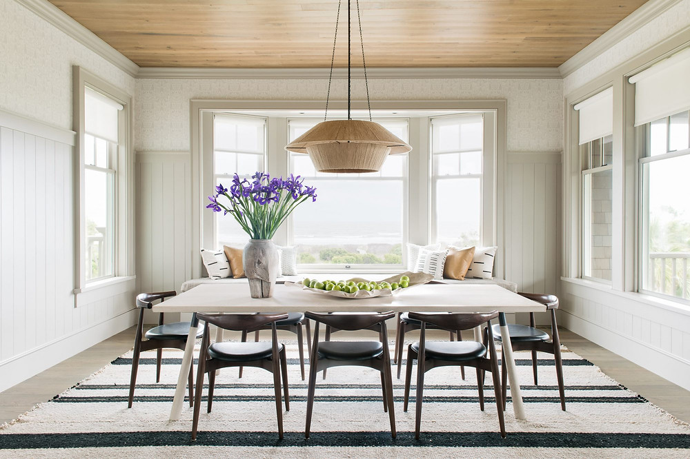 Charming bright and airy Modern Farmhouse Dining Room. View of Atlantic Ocean. Natural pendant over Dining Table. Natural Rug, Timber Ceiling and Shiplap Walls.
