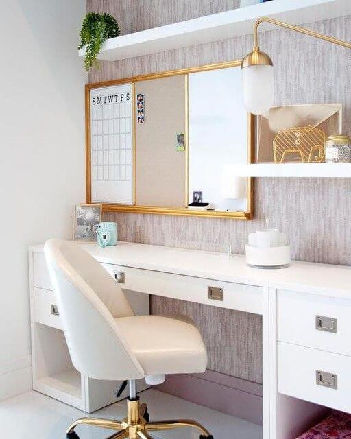 Pottery Barn Teen white campaign style desk with brass-gold hardware. Dusty pink velvet swivel desk chair with brass feet. Mauve wallpaper with white floating shelves decorated with a plant and other brass styling. Cork and marker organisation set off to the left on the wall. Brass and opaque task lighting sconce.