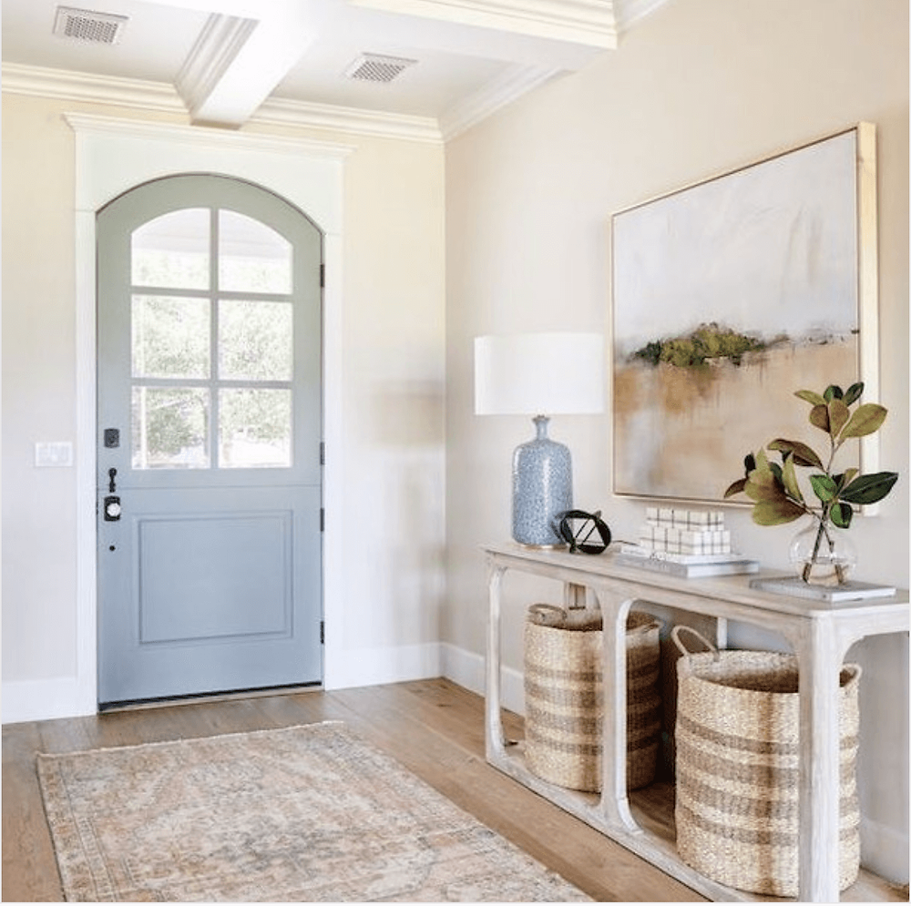 Blue grey arched door, landscape artwork, muted rug, vaulted ceilings. Entry way vignette. Modern Farmhouse style.