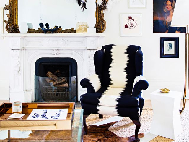 French inspired lounge room with fireplace. Mixed furnishings with antique and modern pieces. Boldly upholstered chair.