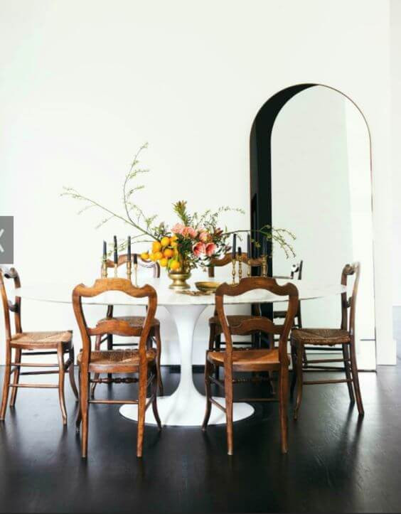 A round white pedestal dining table is surrounded by traditional dark oak dining chairs. A wild flower arrangement in an ornate brass vase sits in the middle of the table surrounded but other vintage brass candlestick holders and black taper candles. The floor is a timber with a very dark stain and the walls are white with an arched doorway with interior of the doorway painted black.