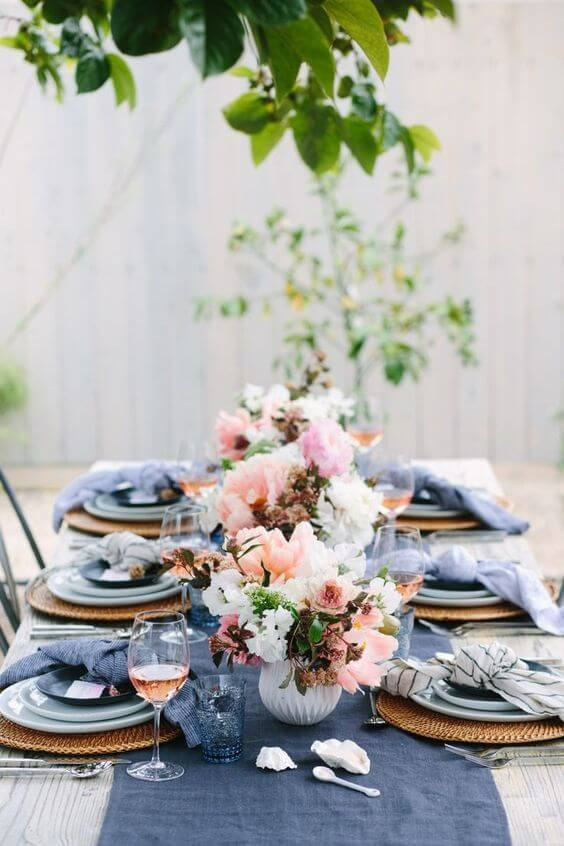 Spring table setting with flowers, deep blue and blush colours.