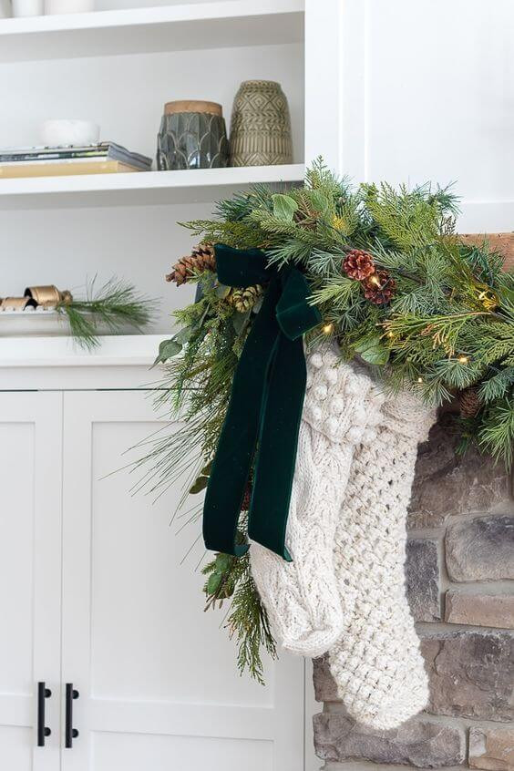 Christmas in July. White rustic stockings hang from a stone fireplace with a green velvet bow and pine garland and twinkle lights.