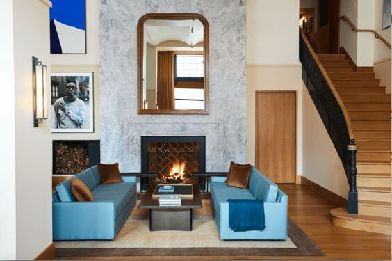 Sinola Hotel in Detroit, MI. Aqua blue sofas with timber, brass and marble accents. Grand marble fireplace.