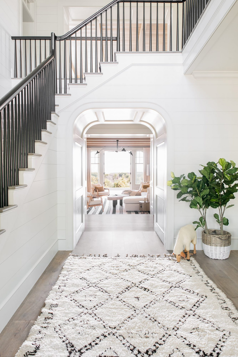 Charming bright and airy foyer. Modern Farmhouse Staircase. Beni Ourain Rug and Shiplap Walls.