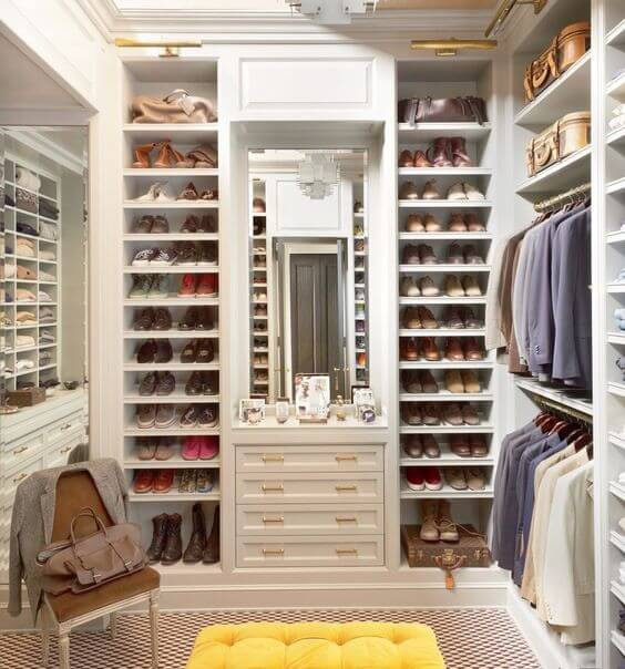 Large walk in closet, yellow tufted bench seat. Men's suits and women's shoes and designer bags.