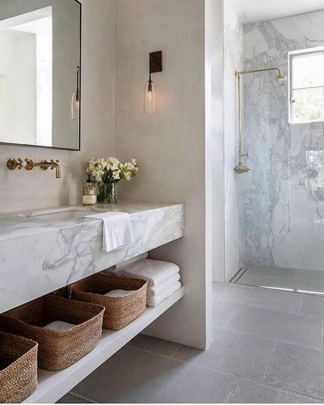 A long marble vanity with an open shelf holding baskets and towels is mounted to a white inset wall. Black sconces flank the sides and black rimmed mirrors hang above traditional style wall mounted brass taps. To the right is a glass shower with a marble wall and brass tapware. On the floor are large light grey ceramic tiles.