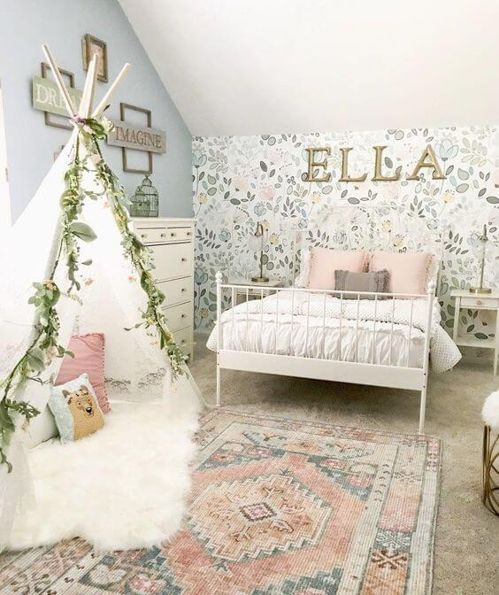 A Little girl's room with the name Ella in a all caps brass lettering hanging over the head of the bed. Light pink, blues and green flowers printed on wallpaper adorne the feature wall behind the bed. The bed is white metal with white bedding and pink and grey throw cushions. White whimsical side tables with matching metal lamps flank the bed and a matching dresser with decorative birdcages sit adjacent to the bed. On the floor sits a child's glamping stye tent decorated with faux plants and flowers. Inside the ten sits a mongolian lamb throw and cushions. The floor covering is wall-to-wall taupe carpeting layered with a bohemian Turkish style rug with pinks and blues.