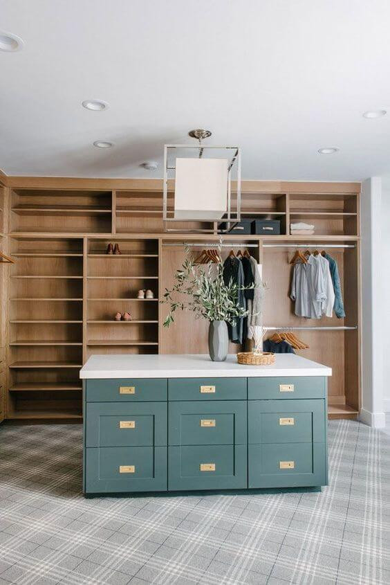 Large master walk-in closet with grey tartan wall-to-wall carpeting. Deep green campaign style island in the middle of the closet with brass hardware and a marble top. Exposed timber built-ins for clothes and white ceiling pendant with down lights.