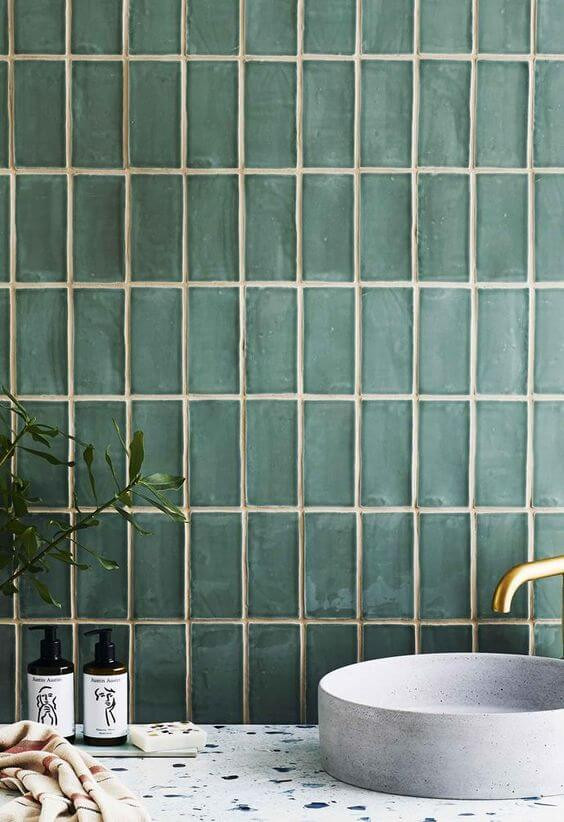 A green glass vertical subway tile backsplash sits behind a terrazzo vanity and with a ceramic basin and a brass tap on top.
