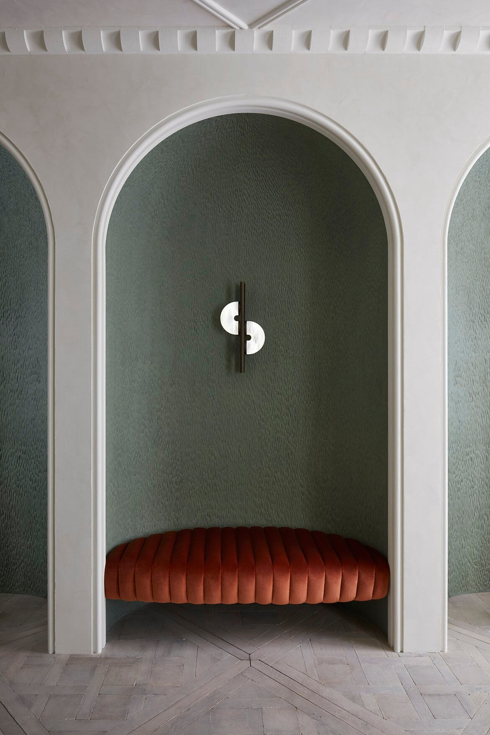 Deep coral coloured tufted bench seat custom placement in arched alcove. Sculptural arched wall sconce light above bench. Timber floors and impressive white cornices.