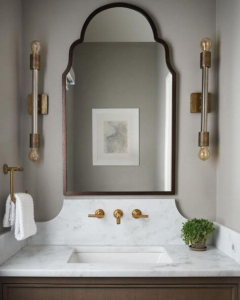 A Moroccan style timber mirror is hanging above a traditional timber vanity with a white marble top and brass hardware. Two brass sconces flank the mirror, and a brass hand town open ring is mounted on the adjacent wall. In the mirror reflects a muted toned abstract artwork in a white frame and matt. A small plant sits next to the sink.