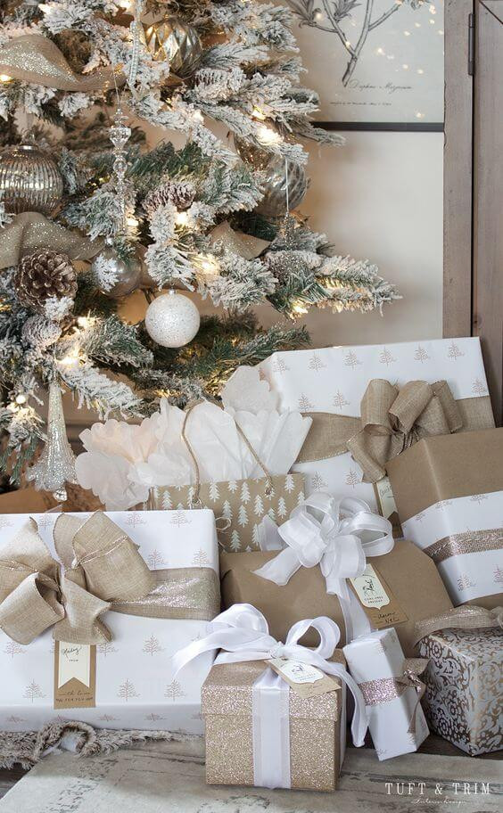 A heavily flocked and decorated Christmas tree sits in a corner with many presents sitting around it. The presents are in brown, white and gold paper with large bows. Christmas in July.