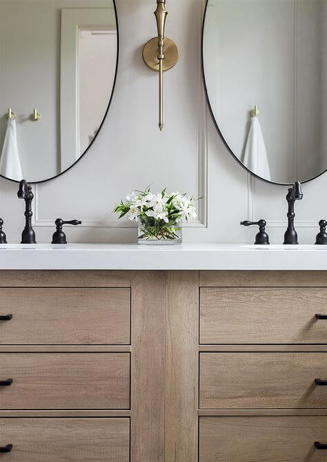 A timber double vanity with six drawers and black hardware has two oval mirrors hanging above. The tapware is an antique bronze and has a traditional shape and sits on top of a marble top. A brass sconce with traditional form is mounted on white wainscoting walls. Flowers in a vase sits between the two sinks.