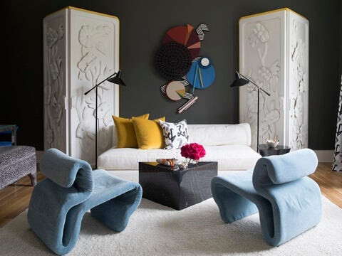 Modern and vintage furnishings. Abstract sculptural wall art. Black arm floor lamps. Black marble coffee table. white sofa. Animal print armchair.