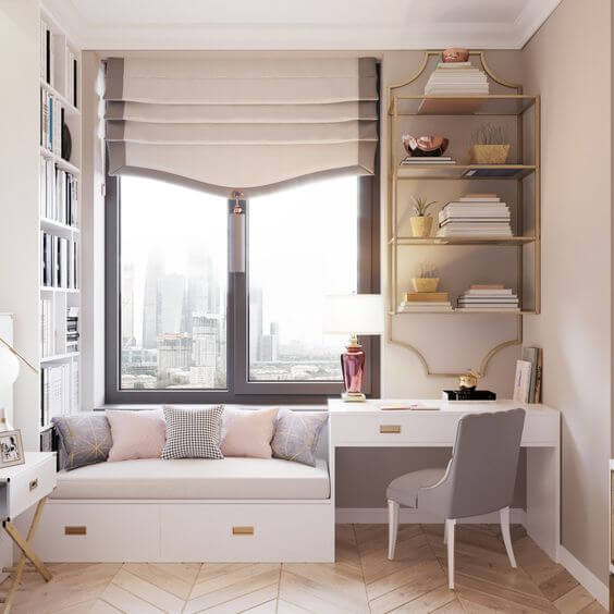 Light and bright office space with window day bed with dusty pink and grey throw cushions. White campaign style desk with brass hardware on the drawers with a grey fabric covered desk chair and brass floating shelves hanging on the grey wall above. On the side wall there is a daybed-to-ceiling bookcase filled with books. The window is black and has a custom white with black trim and tassel roman shade. Parquet chevron oak floors.