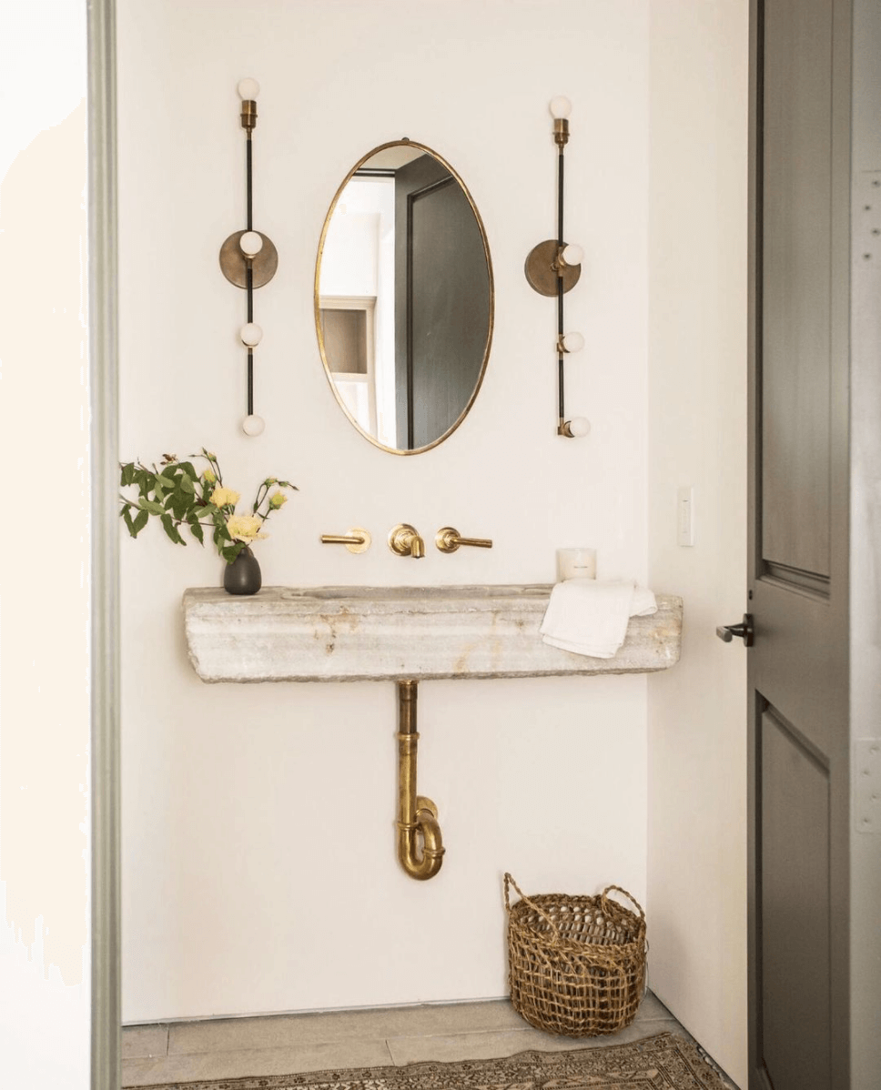 A rough cut limestone sink hangs on the wall of a white powder room. The brass waste pipes are on display and coordinate with the wall mounted brass tapware. On the wall hangs a brass oval mirror flanked by two black and brass light fittings. Flowers sit atop of the stone basin. A woven basket and a vintage rug sit beneath. The entrance door is black. This is an example of Japandi style