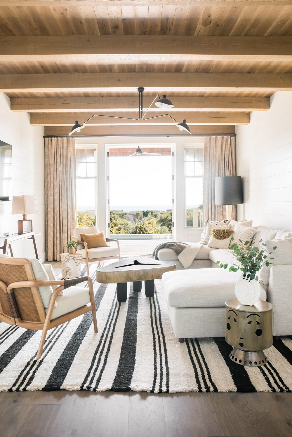 Charming bright and airy Modern Farmhouse. Serge Mouille armed pendant. Natural Rug, Timber Ceiling and Shiplap Walls.