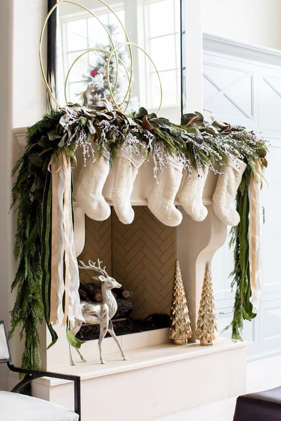A raised traditional fireplace is decorated with pine garland and white rustic stockings. on the hearth sits a metallic reindeer and two metallic christmas trees. Above the mantle sits a black framed modern mirror with three brass rings of various size layered in front and a flocked and decorated Christmas tree reflects from the corner. Christmas in July.