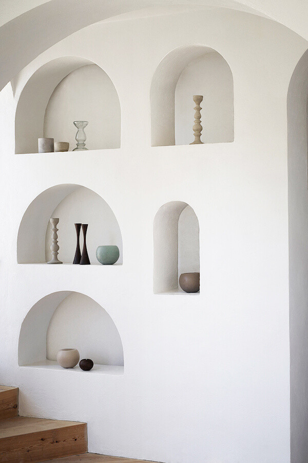 White stucco walls with multiple arch alcoves of various sizes and decorated with sculptural vases and candlestick holders. Timber floors. White arched wall at ceiling.