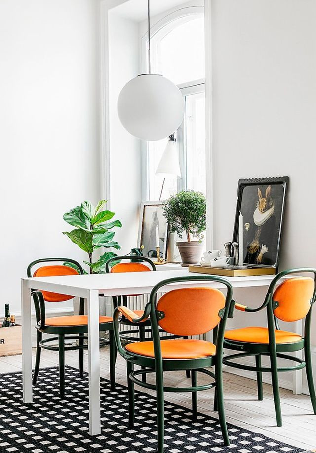 Monochrome dining space with orange upholstered arm chairs. Mix of modern and traditional elements. Cheeky rabbit artwork. Fiddle leaf plant. Modern ball light pendant.