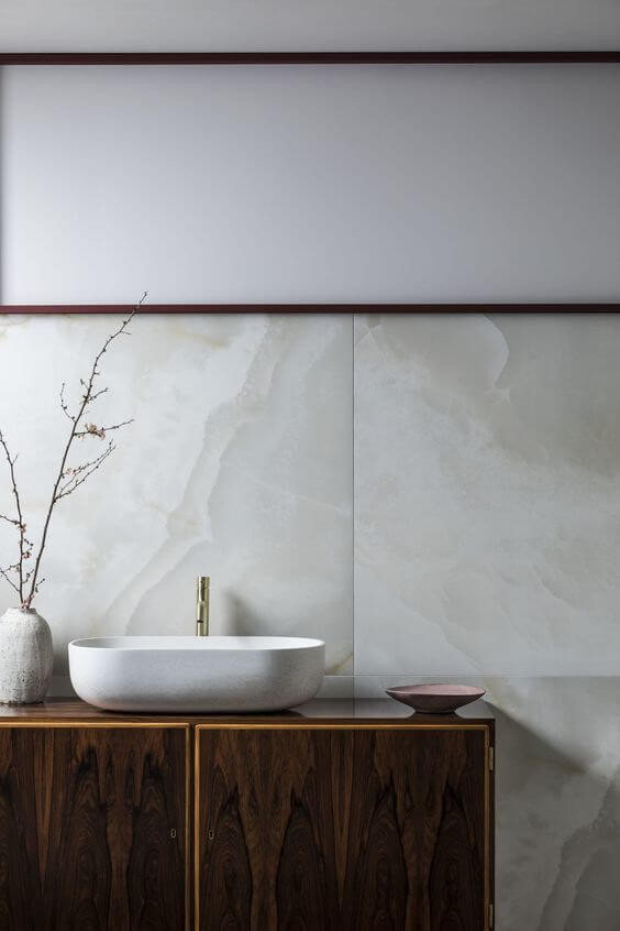 Large porcelain tiles make a backsplash behind a timber vanity with a basin and tap on top. A white vase sits next to the basin holding skinny branches.