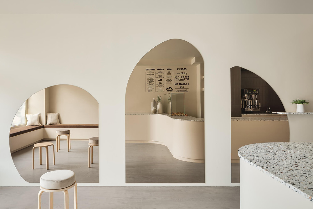 Stylish modern cafe with curved coffee bar, light timber and terrazzo benches. White walls custom window seat with rust coloured cushion. Light timber stools for seating and three large wall mirrors of various arched shapes and sizes.