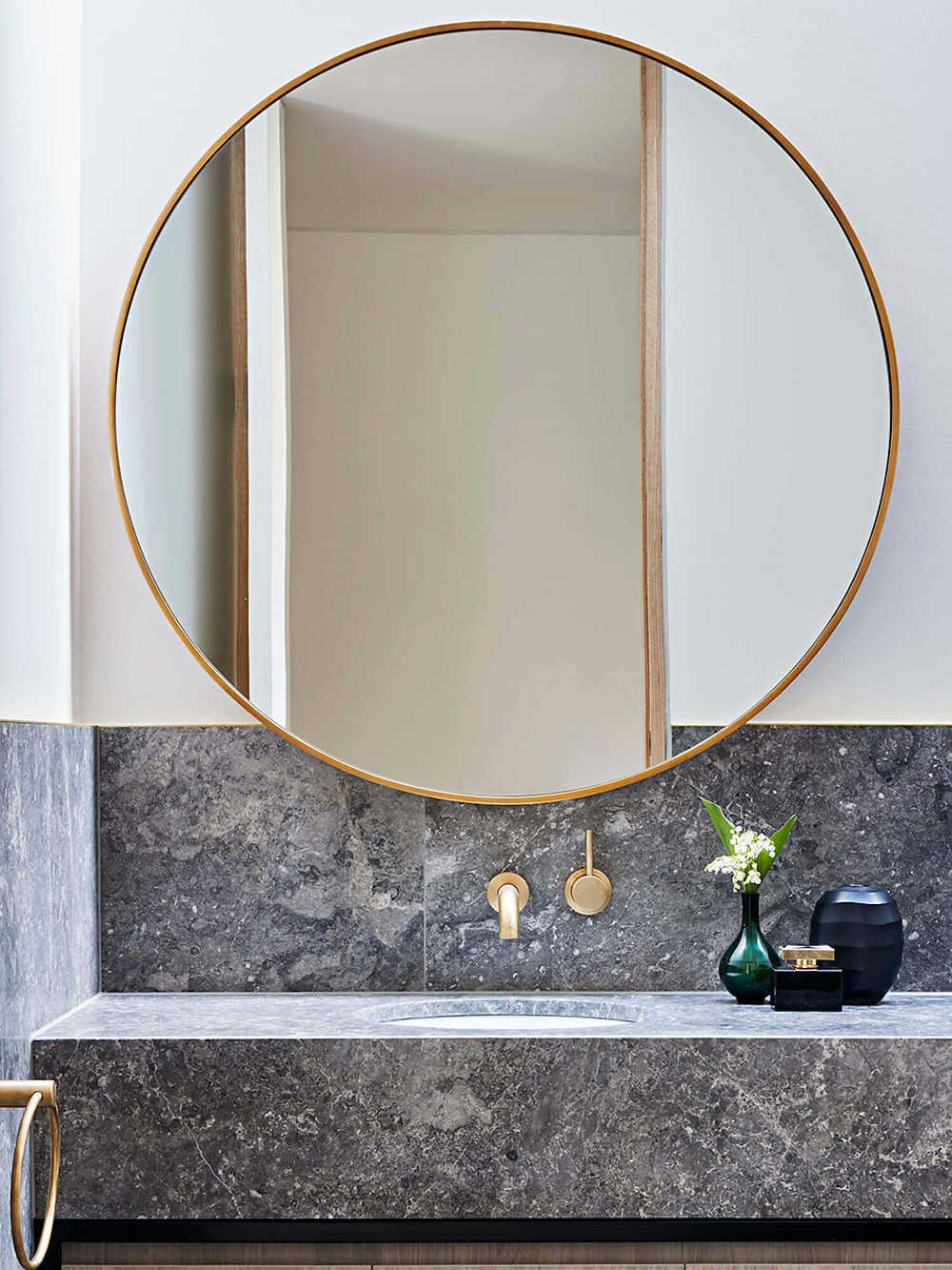 A large round brass mirror hangs above brass wall mounted taps and a large grey marble wall-hung vanity. A brass towel ring is mounted on the left adjacent wall and ceramic vases sit on the vanity to the right, one holding a flower.