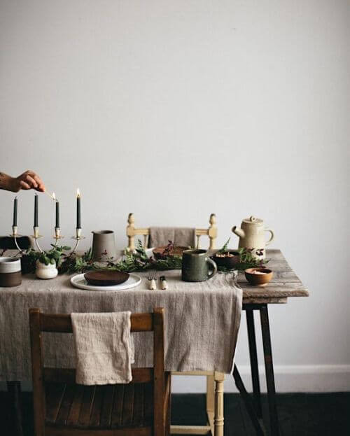 A rustic hygge Christmas dining table dressed with a linen tablecloth that allows part of the rustic timber table to be exposed. A person's hand is seen lighting a black pillar candle being held by a four-pronged candelabra. In the centre is a pine garland table runner and mismatched crockery is set at each seat. Christmas in July.