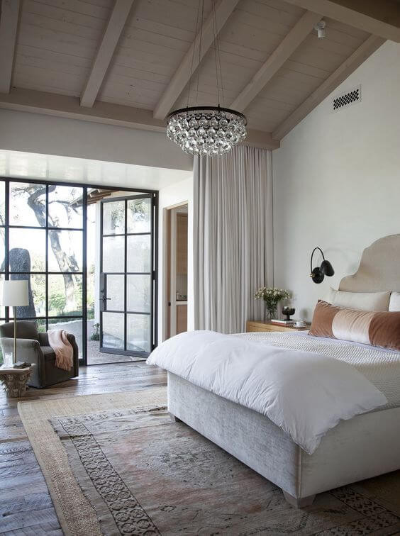 A Spanish/California style master bedroom with exposed timber beams and a glass chandelier hanging from the centre beam over the bed. The master bedroom has large black steel doors that open onto a private patio. The king size bed had a muted curved headboard and is flanked by black wall sconces and timber night stands. On the dark timber floor sits a jute rug, with a smaller vintage Turkish rug layered on top.