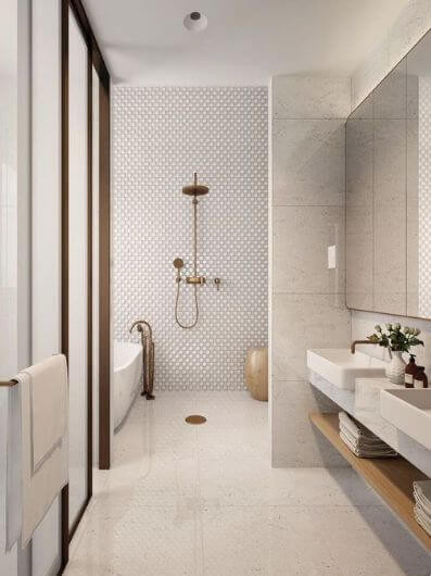 A corridor bathroom has a wall mounted double vanity with a shaving cabinet to the right. Straight ahead a brass shower set is mounted on a textural round white tiled wall. To the left sits a stand alone tub with a floor mounted gooseneck tap.