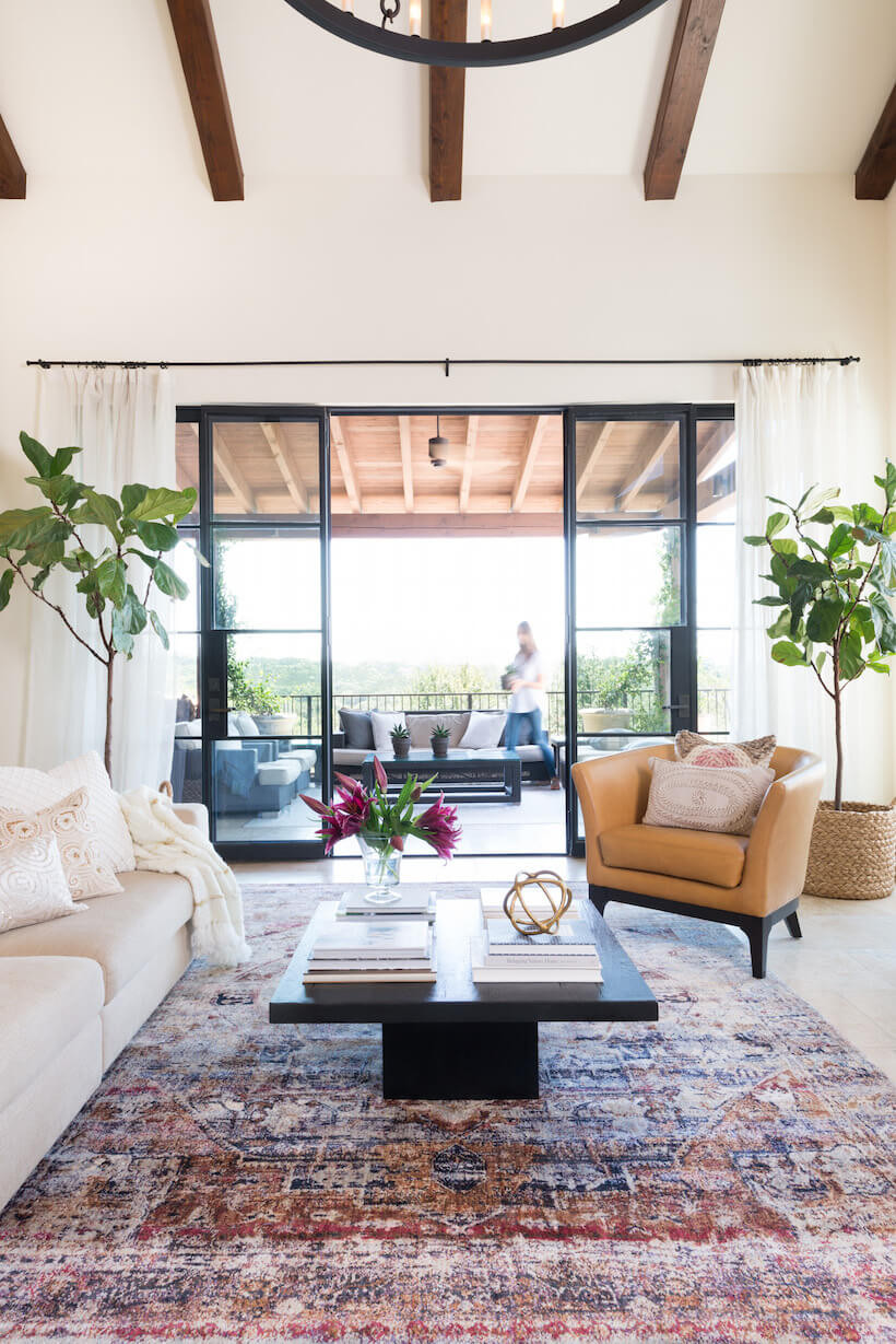 Spanish revival style living room. Exposed dark timber ceiling beams. Large steel doors opening to an outdoor patio with a woman walking by. Two fiddle leaf plants and white drapes flank the doors. Camel-beige leather chair faces a white sofa with white cushions and throw. A dark timber rectangle coffee table sits on top of a deep pink and blue persian style rug.