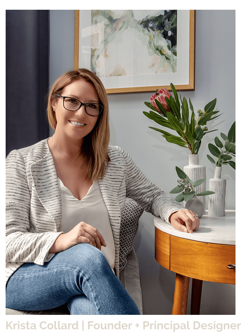 A millennial woman, residential interior designer based on the Lower North Shore of Sydney, Australia. She is wearing a white and grey tweed blazer with a white cami, jeans and black framed glasses. Her hair is dark blonde and she is smiling with her legs crossed and her arm rested on a marble and walnut side table surrounded by native Australian flowers and plants. A watercolour abstract painting in a matted and brass frame hangs on the wall behind her as do charcoal drapes.