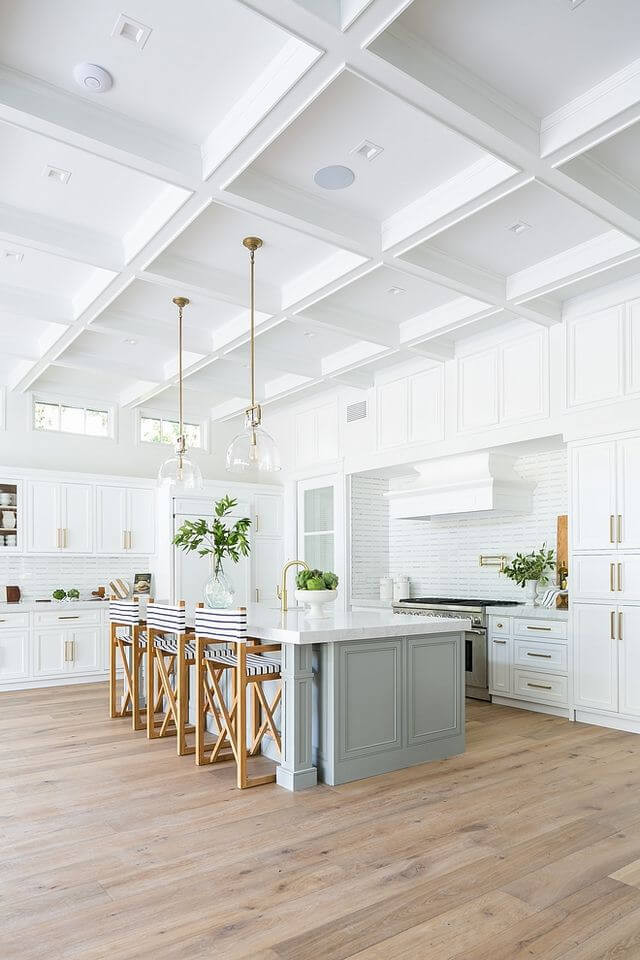 Light blue kitchen island campaign style striped island seating, white shaker cabinetry with brass hardware. Open kitchen with vaulted ceilings, glass island pendants. Bright and airy home.