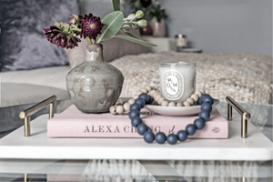 Diptique Mimosa candle styled with Alexa Chung It book and marble and brass tray with beads and flowers.