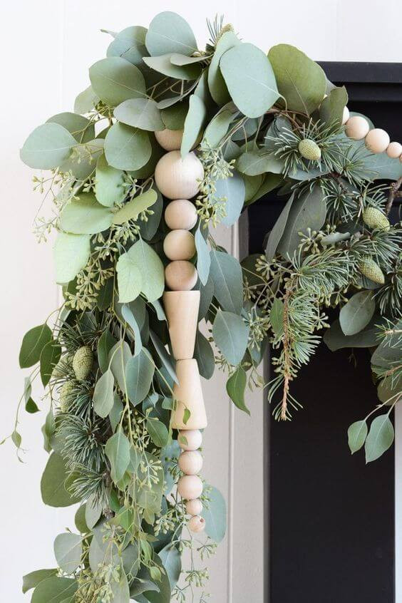 Natural native Australian plants joined together to make a Christmas garland adorn with wood beads drooping over the fireplace.